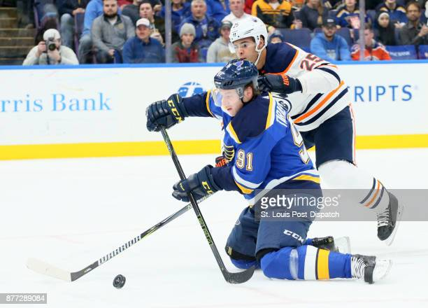 The St Louis Blues' Vladimir Tarasenko tries to play the puck from his knees while being pressured from behind by the Edmonton Oilers' Darnell Nurse...