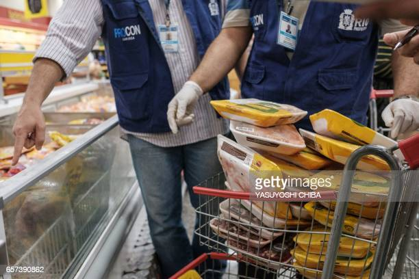 The staff of Rio de Janeiro state's consumer protection agency PROCON inspect and remove chicken products that are not frozen from a freezer at a...