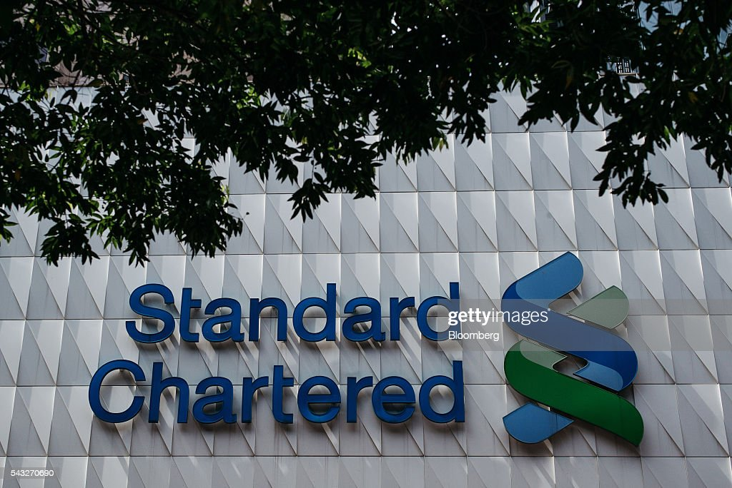 The Standard Chartered Plc logo is displayed at the bank's headquarters building in the Central district of Hong Kong, China, on Monday, June 27, 2016. The aftershocks of the U.K.'s vote to leave the European Union continued to reverberate across financial markets, with the pound extending its selloff near a 31-year low and European equities dropping to levels last seen in February. Asian shares rebounded with commodities. Photographer: Anthony Kwan/Bloomberg via Getty Images