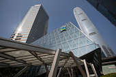 The Standard Chartered Plc logo is displayed atop of a bank branch as it stands between Exchange Square left and Two International Finance Centre in...