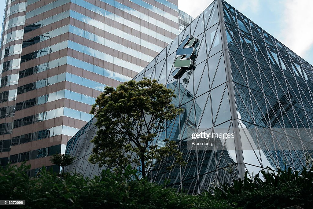 The Standard Chartered Plc logo is displayed atop one of the bank's branch in the Central district of Hong Kong, China, on Monday, June 27, 2016. The aftershocks of the U.K.'s vote to leave the European Union continued to reverberate across financial markets, with the pound extending its selloff near a 31-year low and European equities dropping to levels last seen in February. Asian shares rebounded with commodities. Photographer: Anthony Kwan/Bloomberg via Getty Images