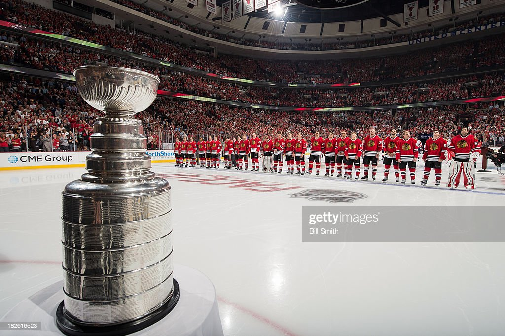 The Stanley Cup sits on the ice, as the Chicago Blackhawks stand behind, during the opening ceremony before the home opener against the Washington Capitals on October 1, 2013 at the United Center in Chicago, Illinois.