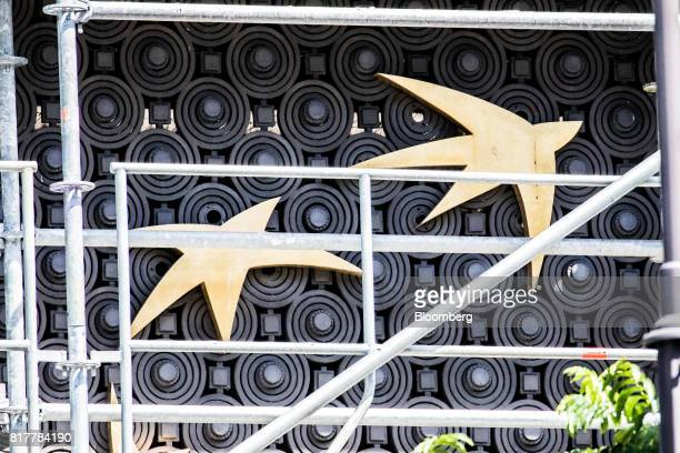 The star and bird of the BNP Paribas SA logo sit on display behind scaffolding outside a BNP Paribas headquarters in Paris France on Tuesday July 18...