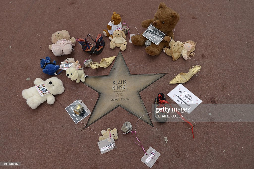 The star of German actor Klaus Kinski is surrounded with dolls and a sign reading 'Thanks Klaus, it doesn't hurt anymore' in Berlin, on February 10, 2013. The action aims to call attention to the allegations against Klaus Kinski to have repeatedly raped his daughter. Actress Nastassja Kinski accused her father of attempting to abuse her, following allegations by her half-sister Pola that he raped her throughout her childhood. AFP PHOTO / GERARD JULIEN