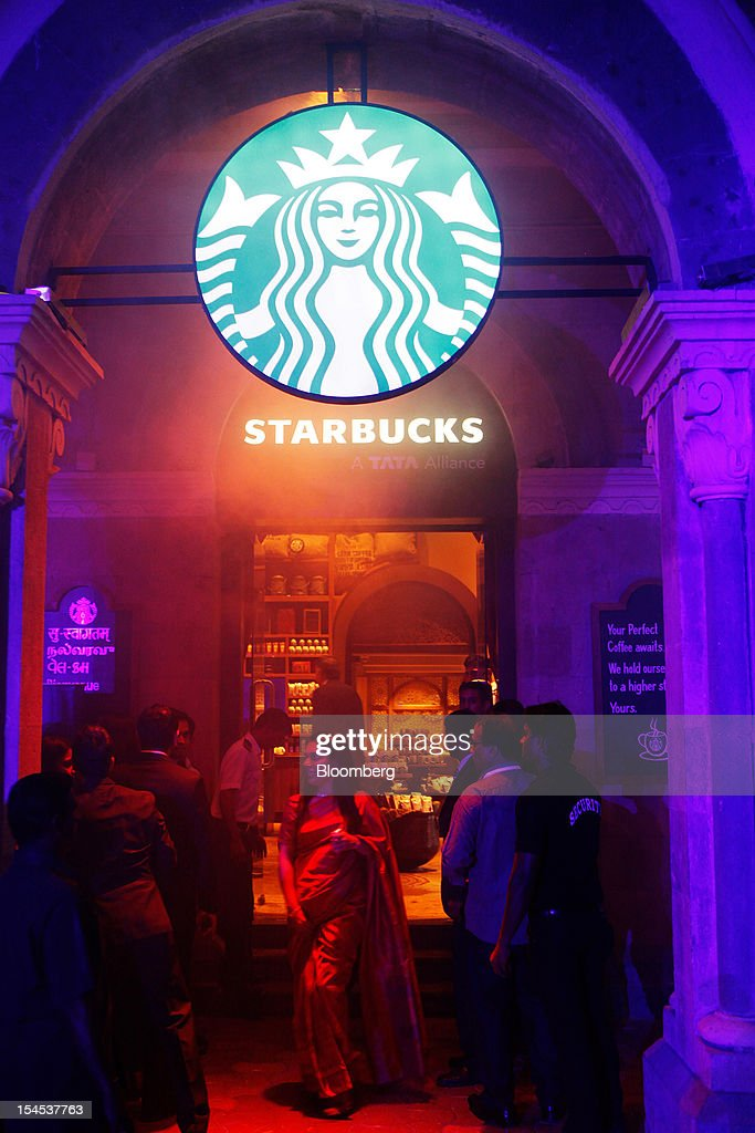 The Starbucks Corp. logo hangs outside the company's first India outlet in Mumbai, India, on Friday, Oct. 19, 2012. Starbucks, which opened its first store in India today, will maintain its partnership with Tata Global Beverages Ltd. and plans to take some of that company's products to new markets, Starbucks' Chief Executive Officer Howard Schultz said. Photographer: Dhiraj Singh/Bloomberg via Getty Images