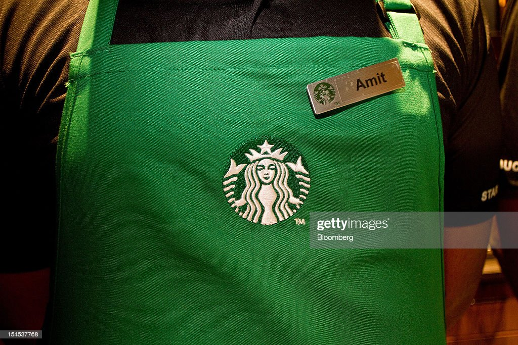 The Starbucks Corp. logo is displayed on an employee's apron at the company's first India outlet in Mumbai, India, on Friday, Oct. 19, 2012. Starbucks, which opened its first store in India today, will maintain its partnership with Tata Global Beverages Ltd. and plans to take some of that company's products to new markets, Starbucks' Chief Executive Officer Howard Schultz said. Photographer: Dhiraj Singh/Bloomberg via Getty Images