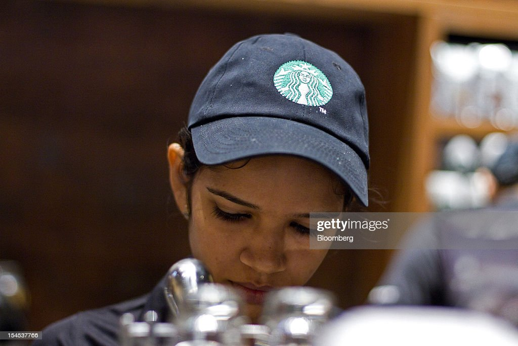 The Starbucks Corp. logo is displayed on an employee's cap at the company's first India outlet in Mumbai, India, on Friday, Oct. 19, 2012. Starbucks, which opened its first store in India today, will maintain its partnership with Tata Global Beverages Ltd. and plans to take some of that company's products to new markets, Starbucks' Chief Executive Officer Howard Schultz said. Photographer: Dhiraj Singh/Bloomberg via Getty Images