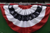 The stars and stripes bunting is affixed to the wall above the thirdbase photopit prior to the Opening Day Game on April 13 2009 between the...