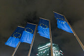 The stars of the European Union sit on banners flying outside the European Central Bank headquarters at night in Frankfurt Germany on Tuesday Oct 6...