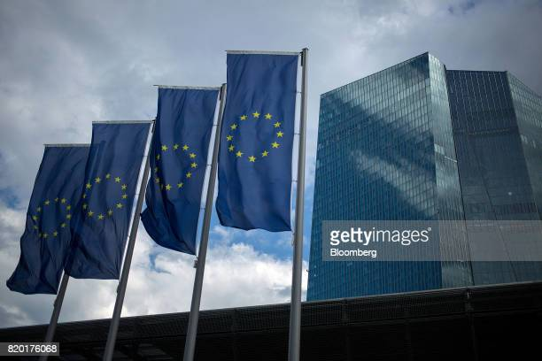 The stars of the European Union sit on banners flying outside the European Central Bank headquarters stands in Frankfurt Germany on Thursday July 20...