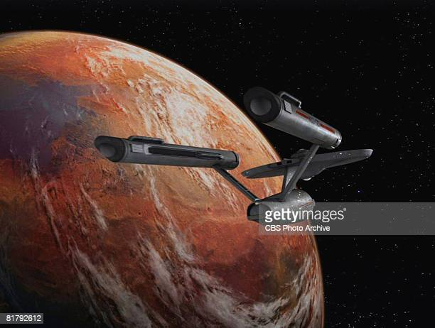 The Starship Enterprise flies over an orange planet in 'The Man Trap' the premiere episode of 'Star Trek' which aired on September 8 1966