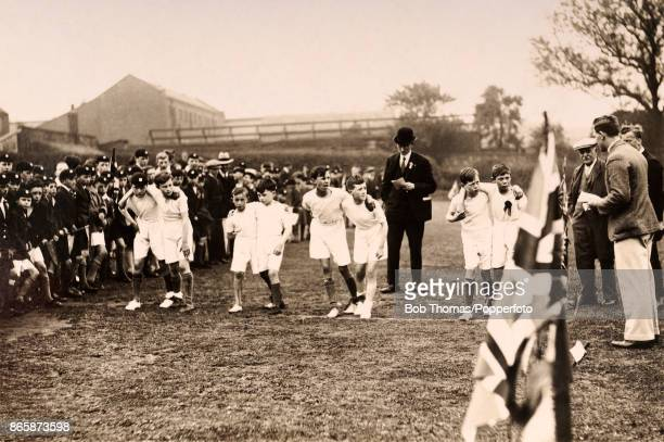 The start of a paired footrace watched by their classmates and teachers at a young boys' school in England circa 1910
