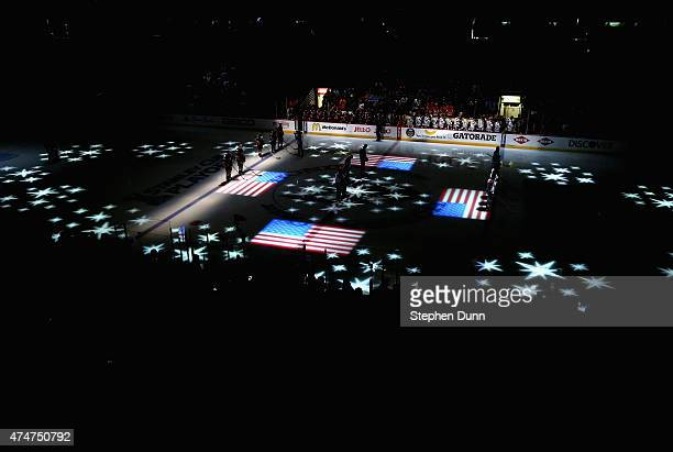 The starting line up for the Anaheim Ducks and the Chicago Blackhawks stand on the ice during the singing of the national anthem before playing in...