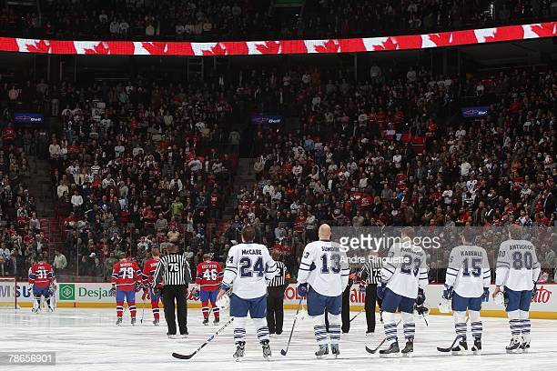 The starting lineup of the Toronto Maple Leafs stand at the blue line during the singing of the National Anthem before a game against the Montreal...