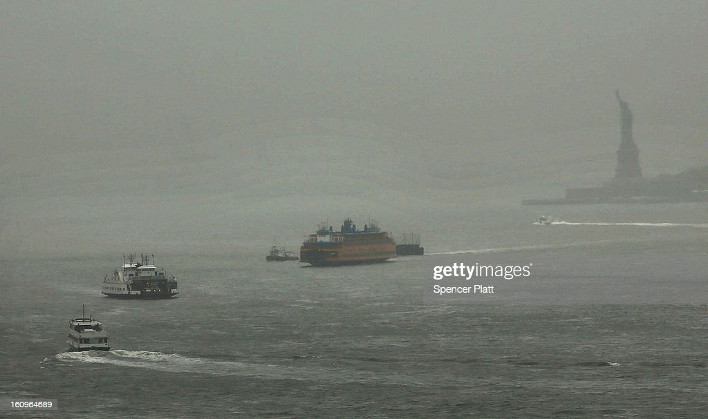 The Staten Island Ferry mmoves across New York Harbor as Statue of Liberty stands in a cloud of snow and sleet in the early hours of a major winter storm on February 8, 2013 in Brooklyn borough of New York City. New York City and much of the Northeast is expected to get a foot or more of snow through Saturday afternoon with possible record-setting blizzard conditions expected in Boston, Massachusetts. Heavy snow warnings are in effect from New Jersey through southern Maine.