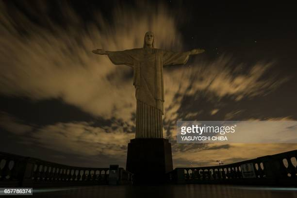 The statue of Christ the Redeemer is seen after being plunged into darkness for the Earth Hour environmental campaign on top of Corcovado hill in Rio...
