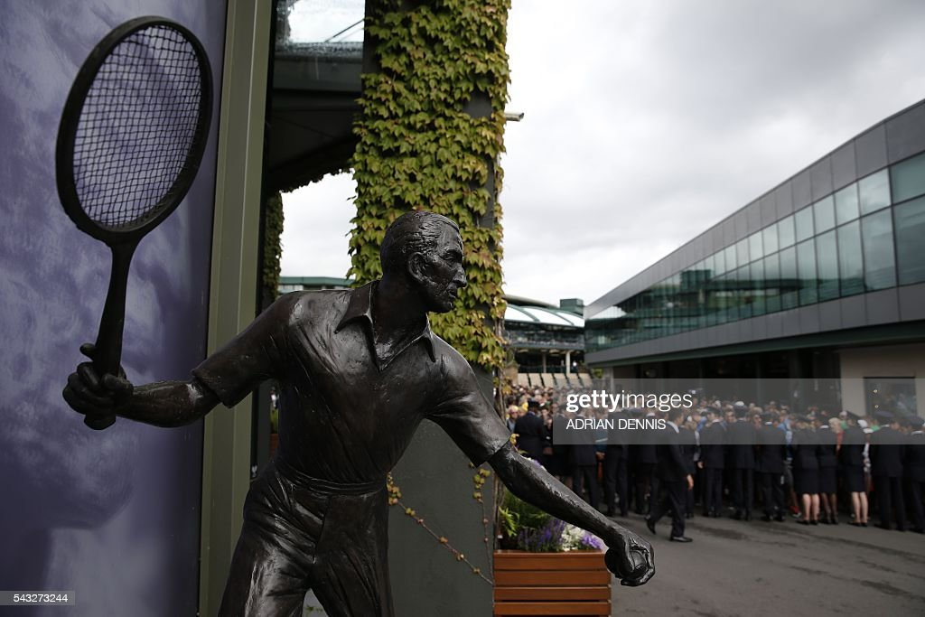 The statue of Fred Perry is seen as spectators queue to enter The All England Lawn Tennis Club in Wimbledon, southwest London, on June 27, 2016 on the first day of the 2016 Wimbledon Championships. / AFP / ADRIAN