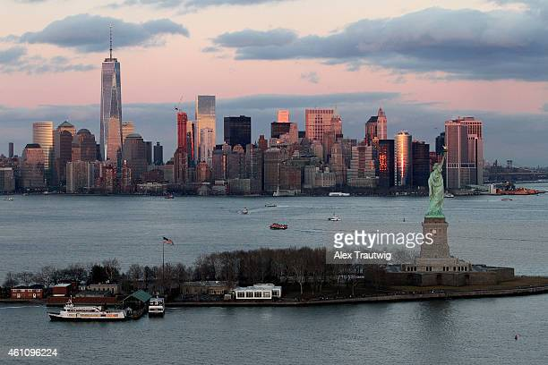 The Statue of Liberty and One World Trade Center are seen at sunset from above on December 30 2014 in New York City