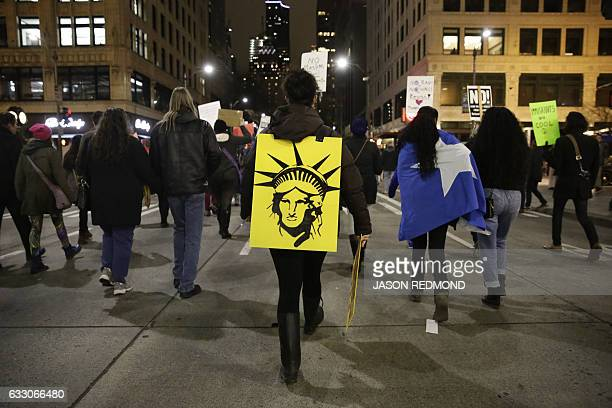 The Statue of Liberty is pictured on a sign as people march in support of immigrants and refugees in Seattle Washington on January 29 2017 US...