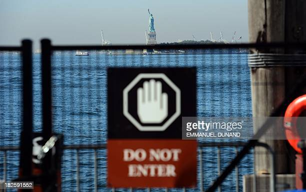 The Statue of Liberty stands empty of visitors after it closed due to a US government shutdown in New York October 1 2013 Government institutions and...