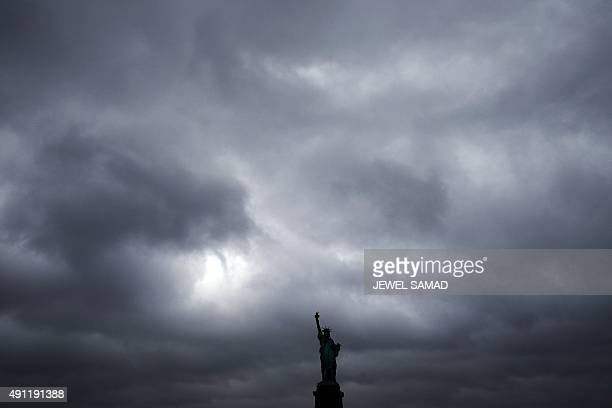 The Statue of Liberty stands tall as cloud hover over it in New York on October 3 2015 AFP PHOTO/JEWEL SAMAD