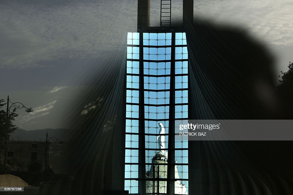 The statue of Our Lady of Lebanon is seen reflected in a window of the basilica in the town of Harissa north East of Beirut as pilgrims flock to the shrine marking the start of the Holy Month of Virgin Mary on May 1, 2016. Virgin Mary is considered one of the most righteous and greatest women in Islam and is venerated by both Islam and Christianity. / AFP / PATRICK BAZ