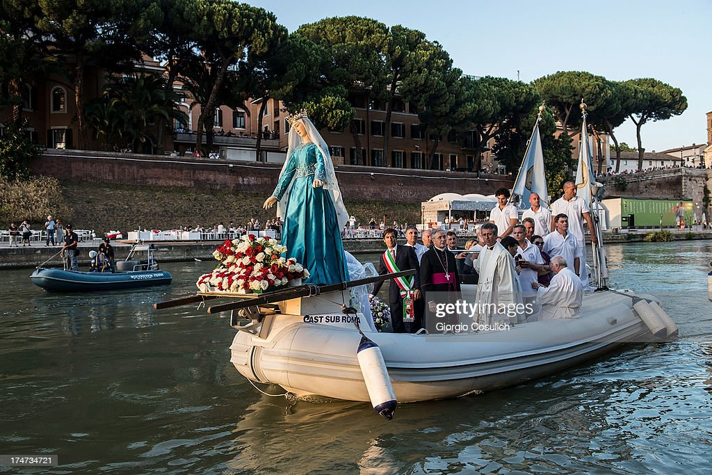 The statue of the 'Madonna della Fiumarola' (or Madonna del Carmine) docks on the banks of the Tiber after being carried in procession on a boat along the river, during the closing of the annual 'Festa de Noantri', in the Trastevere district on July 28, 2013 in Rome, Italy. Every year on the last Sunday of July, Romans reenact this historical procession along the river Tevere to Trastevere. The statue that is reported to have been found in 1535 at the mouth of the river, was donated to the Carmelite friars of the church of S. Grisogono, and since then acts as protector of the inhabitants of Trastevere quartier.