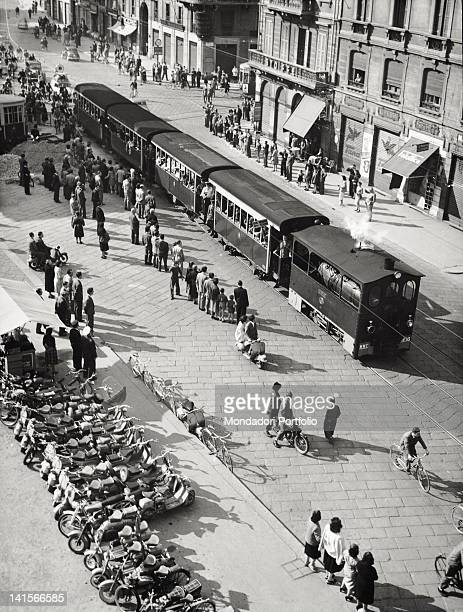The steam tram 'Gamba de Legn' going through a city's street Many onlooker Italian people watching it Milan 1950s