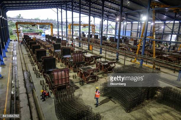The steel reinforcing frames of precast concrete tunnel segments sits stacked near molds at the Mumbai Metro Rail Corp casting yard in Mumbai India...