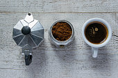 The steps to make the cafe. Top view of  moka - italian coffee maker and coffee cup on wooden white background