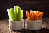 The sticks of carrots and celery on wooden table.