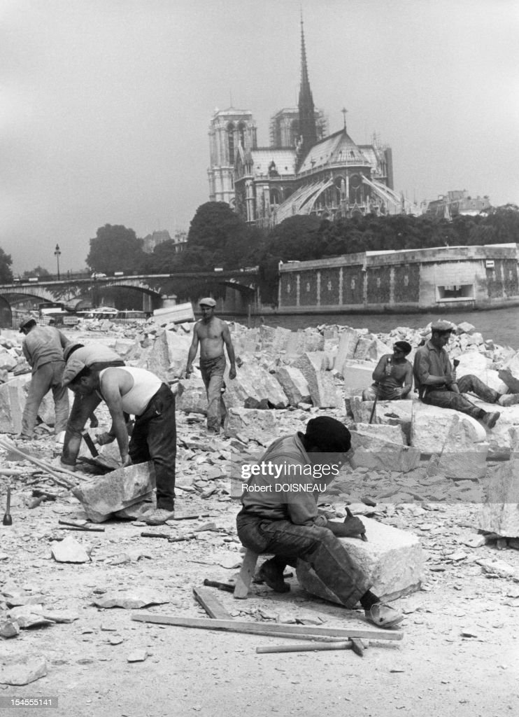 The stone-cutters on the banks of the Seine river on the quai de la Tournelle, in front of Notre Dame, 1969 in Paris, France.