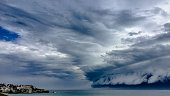 Huge storm cloud hovering over the ocean.