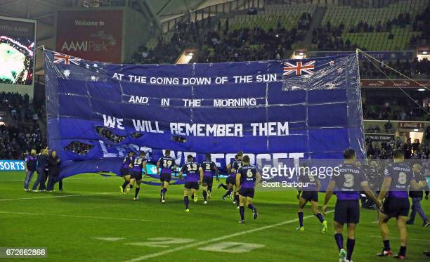 The Storm runs with the ball through their banner during the round eight NRL Anzac Day match between the Melbourne Storm and the New Zealand Warriors...