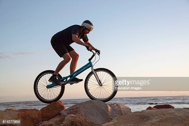 The Strand Western Cape South Africa A mountain Bike Rider Skillfully Riding Over Rocks on The Shoreline at The Strand In The Western Cape