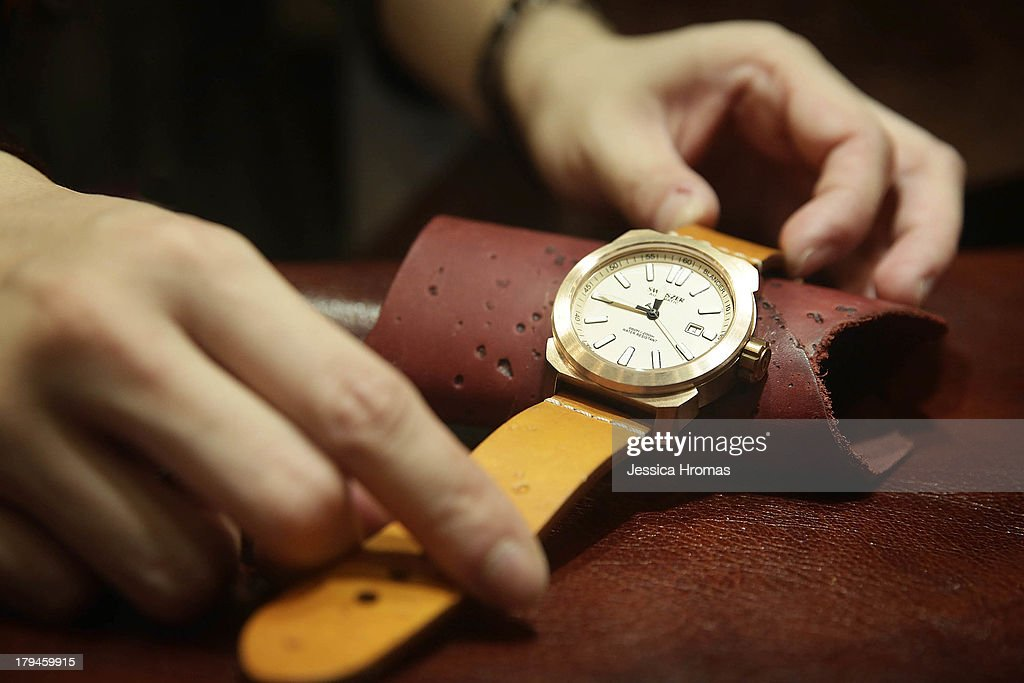 The strap of a mens bronze Switszer watch, valued at USD $850 is sdjusted on the Global Line Limited Stand at the Hong Kong Watch And Clock Fair on September 4, 2013 in Hong Kong, Hong Kong.
