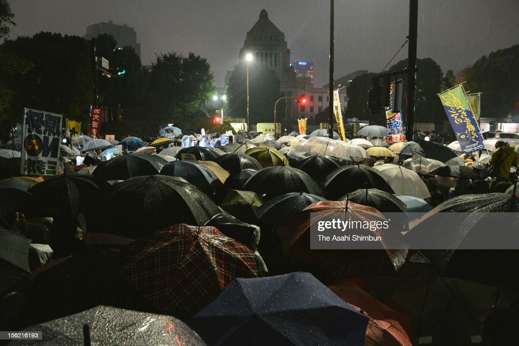 The street in front of the Diet Building filled with crowds of Japanese citizens with umbrellas, protesting against reactivation of nuclear plants on November 11, 2012 in Tokyo, Japan.