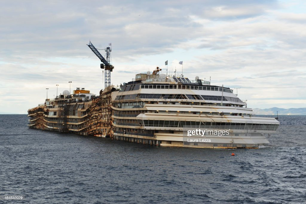 The stricken Costa Concordia cruise ship remains in the water on January 22 2014 in Isola del Giglio Italy Tomorrow for the first time since the...