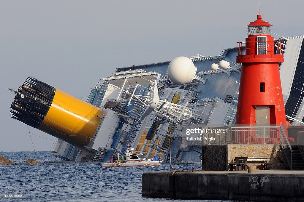 The stricken cruise ship Costa Concordia viewed from the port as relatives and friends of victims of Friday's shipping disaster arrive at Giglio...