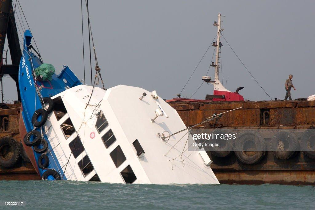 The stricken ferry is pulled out of the water near Yung Shue Wan on Lamma Island on October 2, 2012 in Hong Kong. Thirty-six passengers have been killed and several others were injured when a Hong Kong Electric ferry, carrying 124 people, collided with a tug boat off the coast of Hong Kong late on Monday.