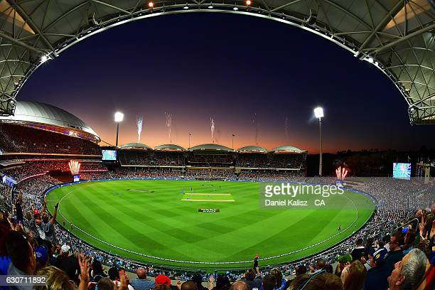 The Strikers players celebrate the fall of a wicket as fireworks can be seen at sunset during the Big Bash League match between the Adelaide Strikers...
