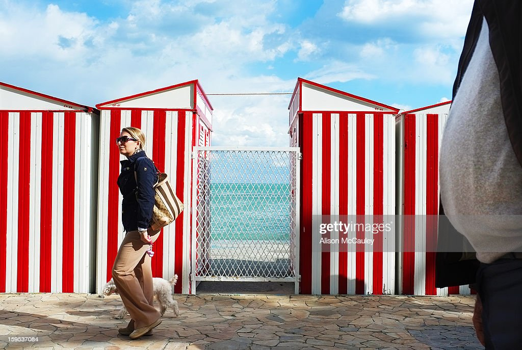 CONTENT] The striped red and white beach huts are set against a blue and fluffy white clouded sky. The turquoise sea can be seen between the huts. A young woman with a dog stroll by. The rotund belly of a man enters and fills the right hand edge of the image.