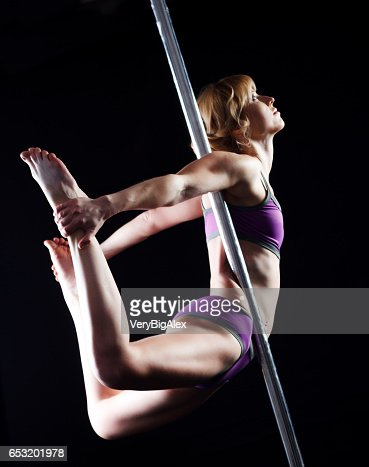 The strong and graceful young girl performing acrobatic exercises on pylon : Stock Photo