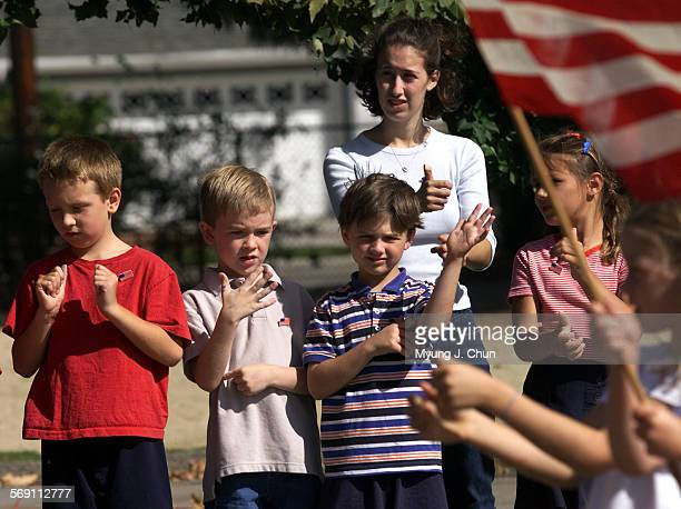 The student body and faculty at CHIME Charter Elementary School in Northridge recite the Pledge of Allegiance in sign language Friday morning as part...