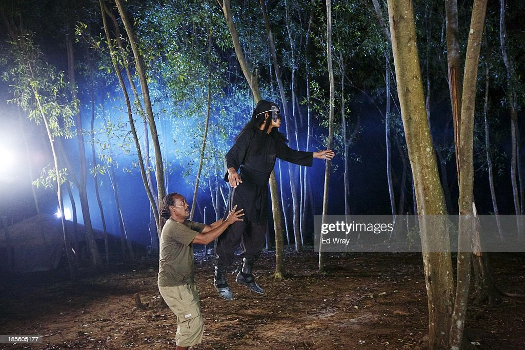 The stunt coordinator works with a stuntman to get a flying stunt filmed during the production of Ciung Wanara, one of the many Indonesian soap operas based on traditional Indonesian legends on October 21, 2013 in Cileungsi, Indonesia. The stories often involving kings, dragons, evil ministers, witches, gods and heroes, which were traditionally performed as shadow puppet plays and by professional storytellers, have a huge audience who have embraced the complex stories, much as western audiences have taken to the fictional intrigue of Game of Thrones.