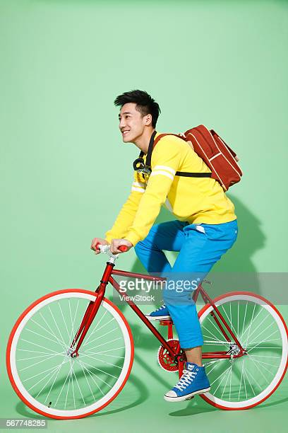 The stylish young man riding a bicycle