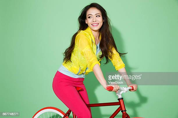 The stylish young woman riding a bicycle