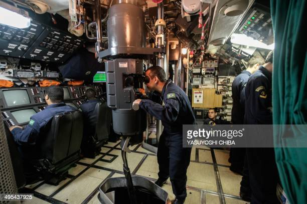 The submarine commander watches through the periscope of the BNS S34 Tikuna Brazilian dieselelectric powered type 209 attack submarine during a drill...