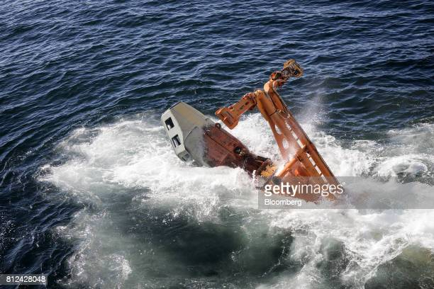 The suction rig of the 'crawler' tractor drops into the sea from the deck of the Mafuta diamond mining vessel operated by Debmarine Namibia a joint...