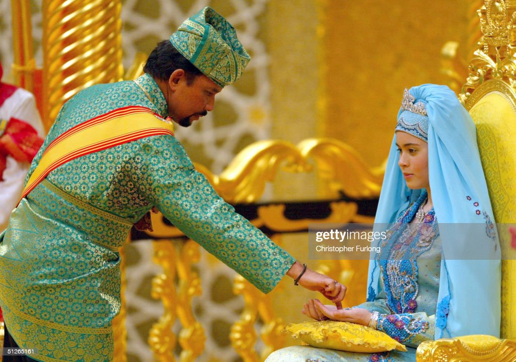 BEGAWAN, BRUNEI - SEPTEMBER 5. The Sultan of Brunei anoints the hands of Princess Dayangku Sarah binti Pengiran Salleh Ab Rahaman during the powdering ceremony of the wedding couple at The Sultans Palace September 5, 2004 in Bandar Seri Begawan, Brunei. His Royal Highness Prince Haji Al-Muhtadee Billah ibni Sultan Haji Hassanal Bolkiah Mu?izzaddin Waddaulah, the Crown Prince of Brunei Darussalam and his bride Princess Dayangku Sarah binti Pengiran Salleh Ab Rahaman were taking part in the traditional ceremony of Majlis Istiadat Berbedak Pengantin Diraja. The Royal couple is anointed with herbs and pastes as part of the many traditional events leading up to the culmination of wedding ceremony on Wednesday.